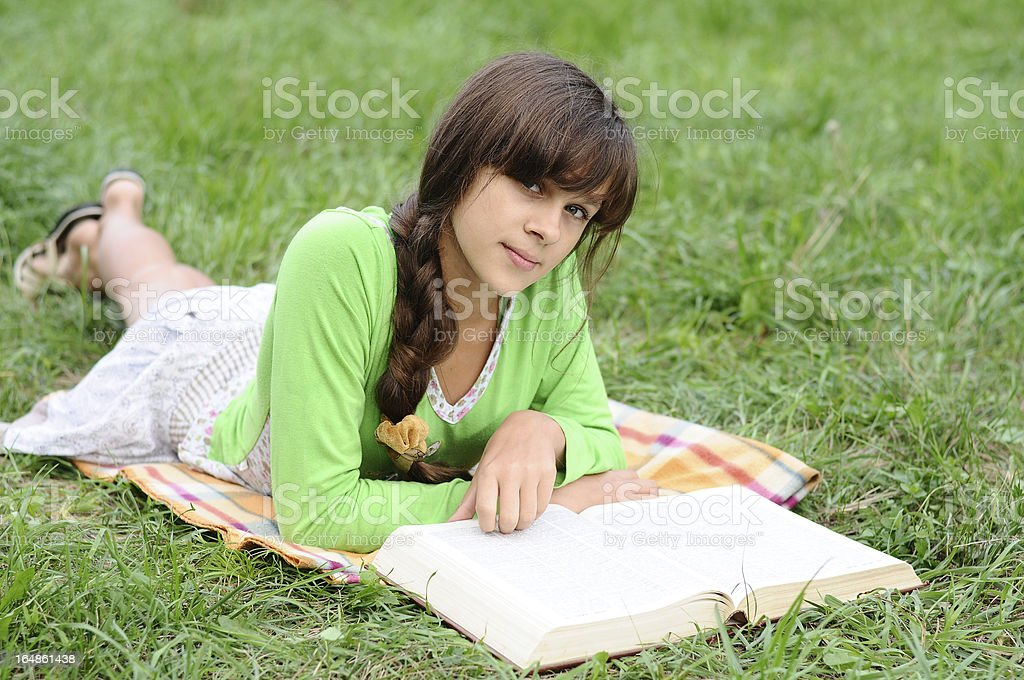 Girl reading a book lying on the grass royalty-free stock photo