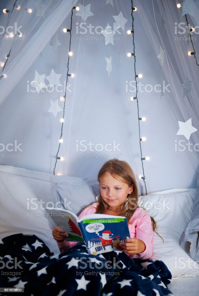 Girl reading a book on bed stock photo