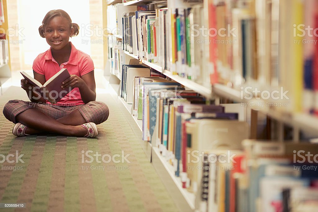 Girl reading at the library stock photo