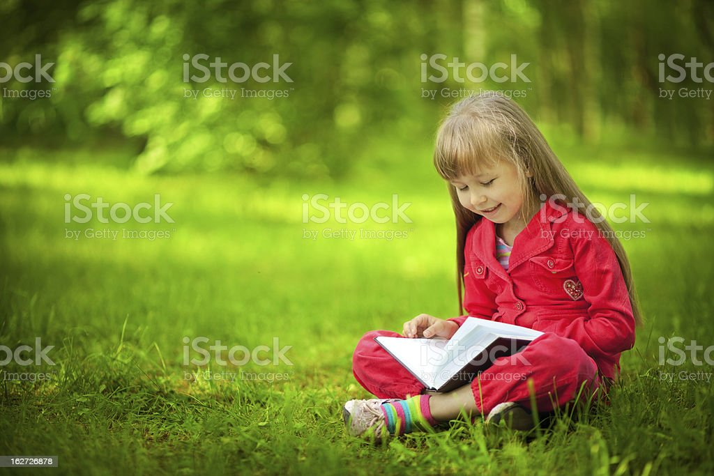 Girl reading book in park royalty-free stock photo