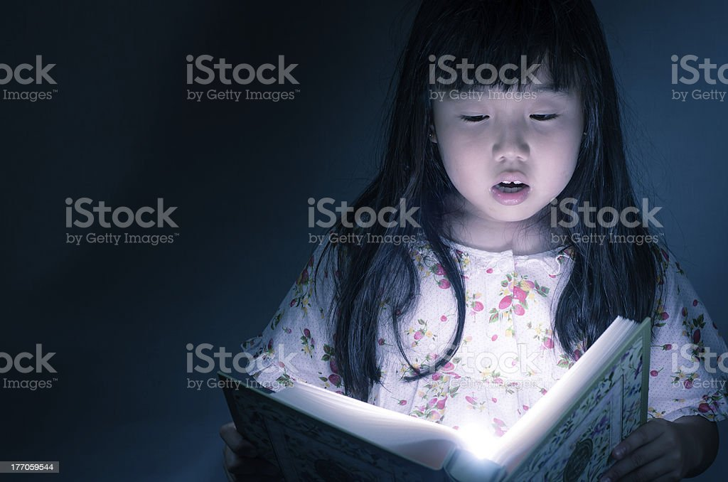 Girl reading  book in the dark background royalty-free stock photo