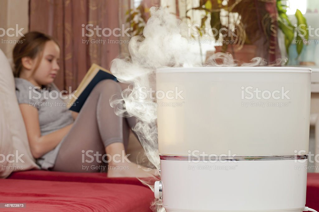 Girl reading book on the background of humidifier stock photo