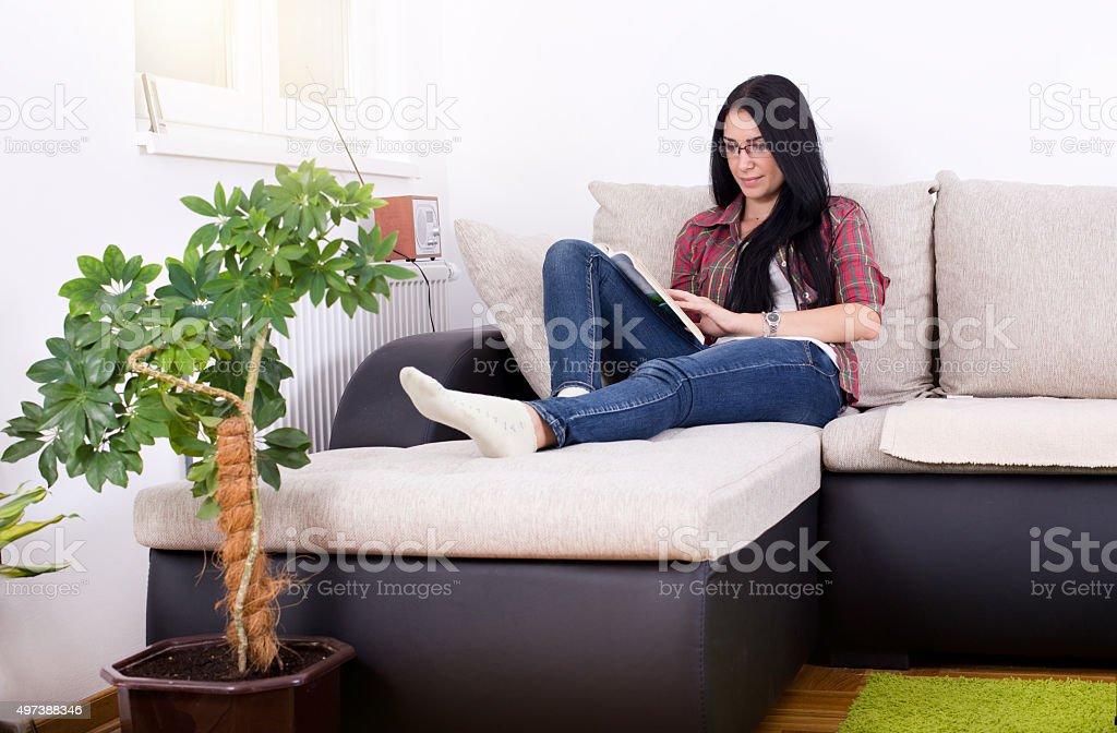 Girl reading book on the sofa stock photo