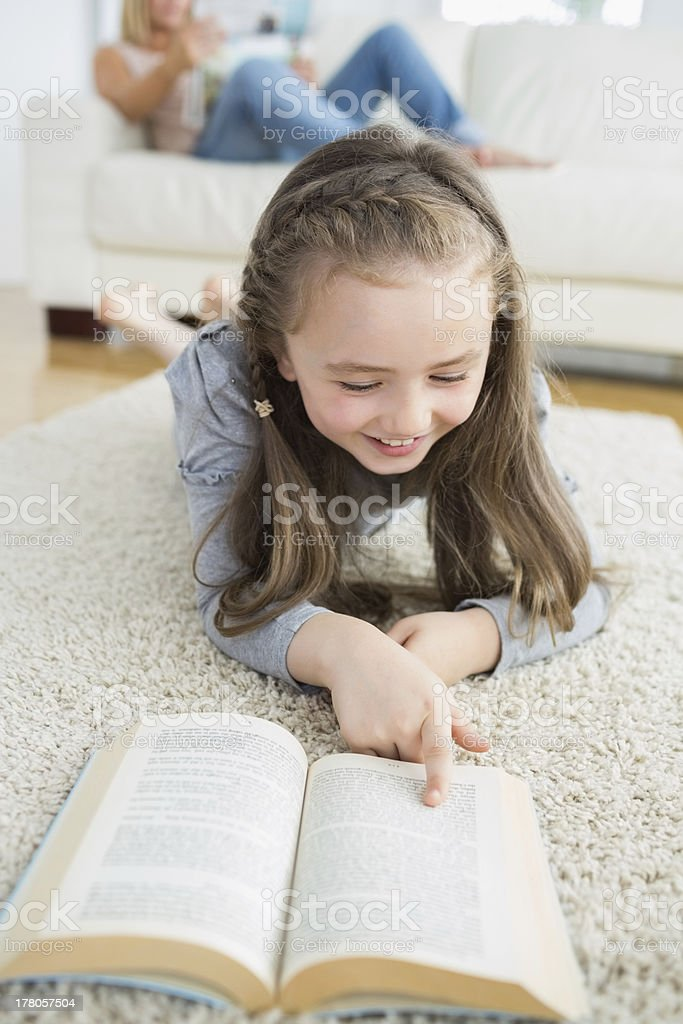 Girl reading book with her mother looking the newspaper royalty-free stock photo