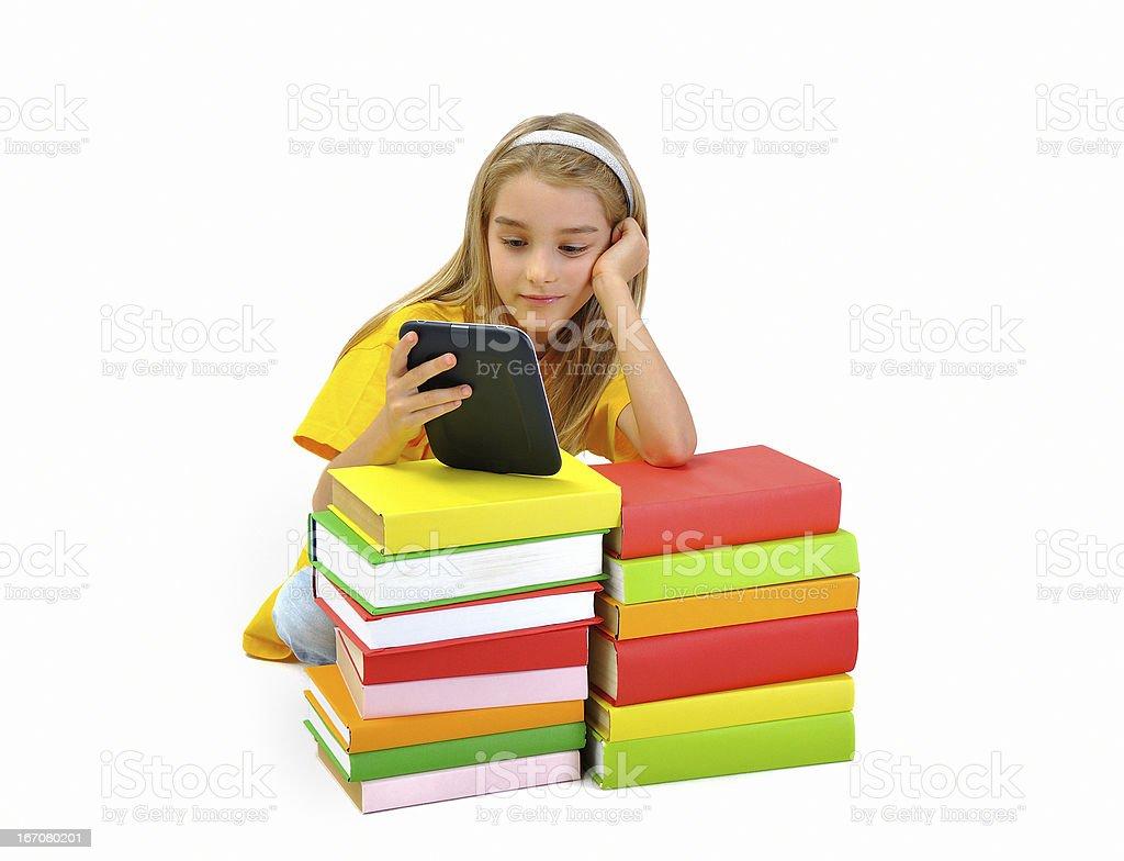 Girl reading e-book among books royalty-free stock photo