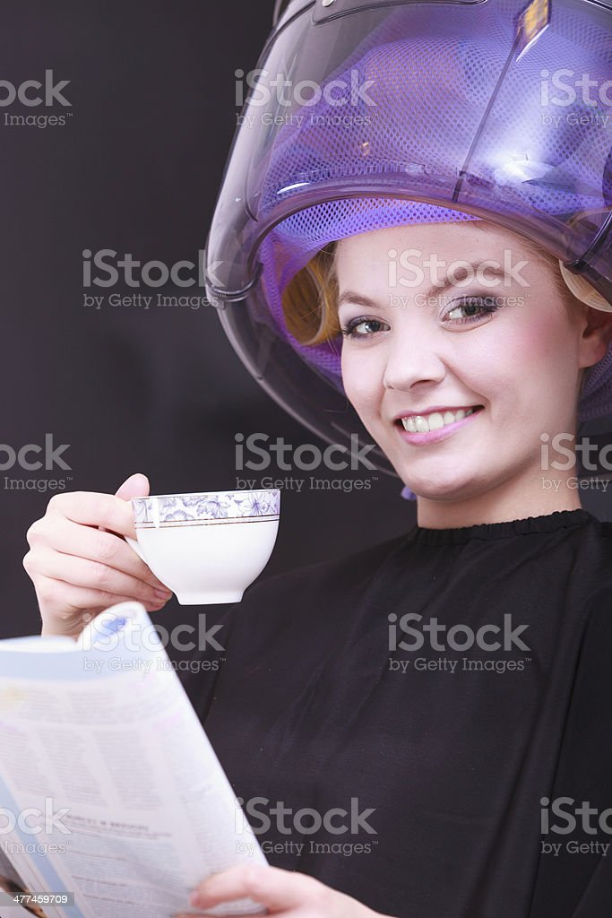 Girl reading magazine drinking coffee. Hairdryer in hair beauty salon royalty-free stock photo
