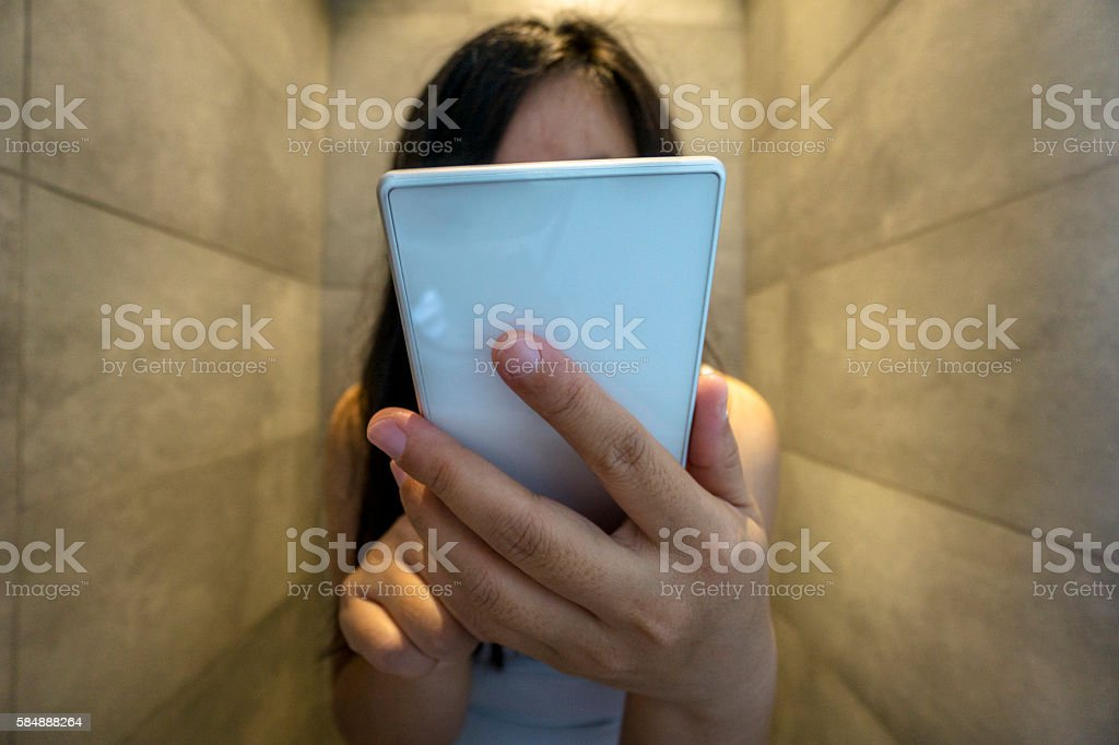 girl reading smart phone in toilet stock photo