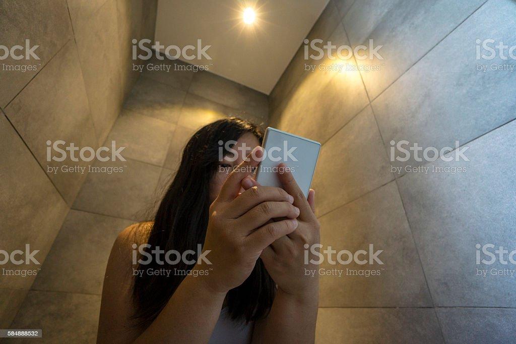 girl reading smart phone in toilet stock photo