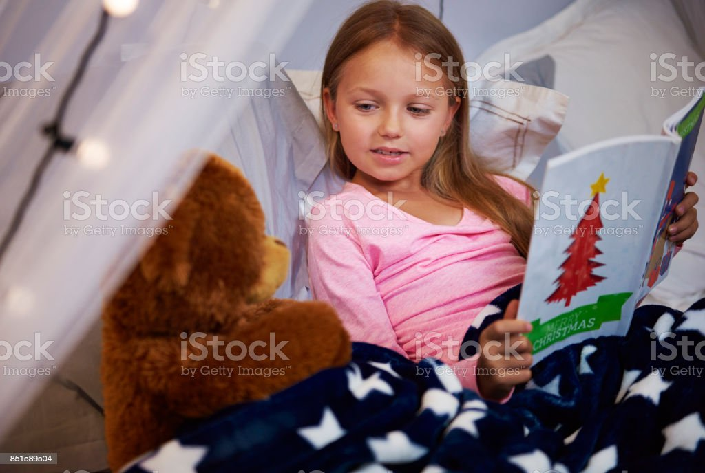 Girl reading storybook with her a teddy bear stock photo