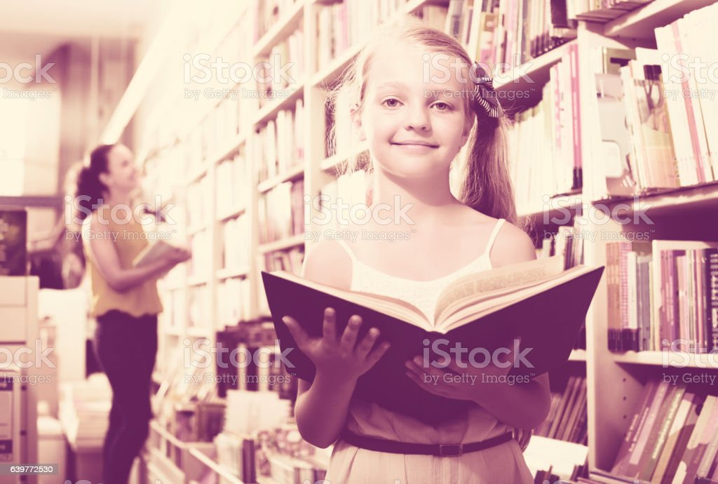 Girl reading textbook in bookstore stock photo