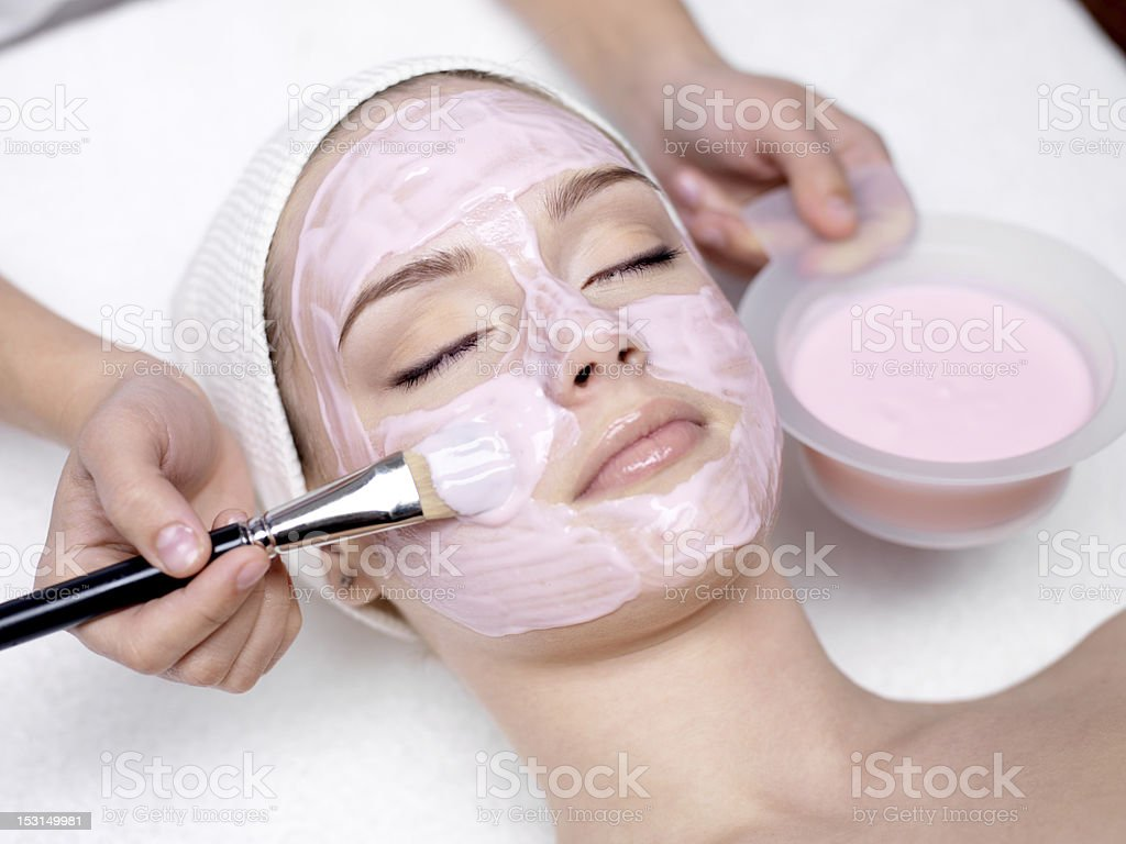 Girl receiving cosmetic pink facial mask stock photo