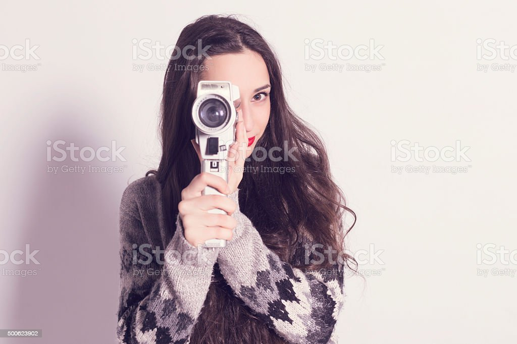 Girl recording with a very old super 8mm camera stock photo
