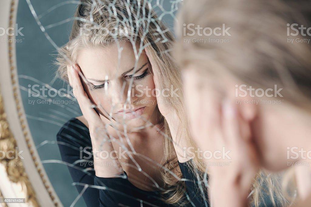 Girl reflected in broken mirror stock photo