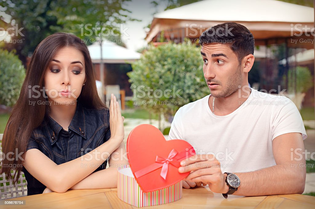Girl Refusing Heart Shaped Gift From Her Boyfriend stock photo