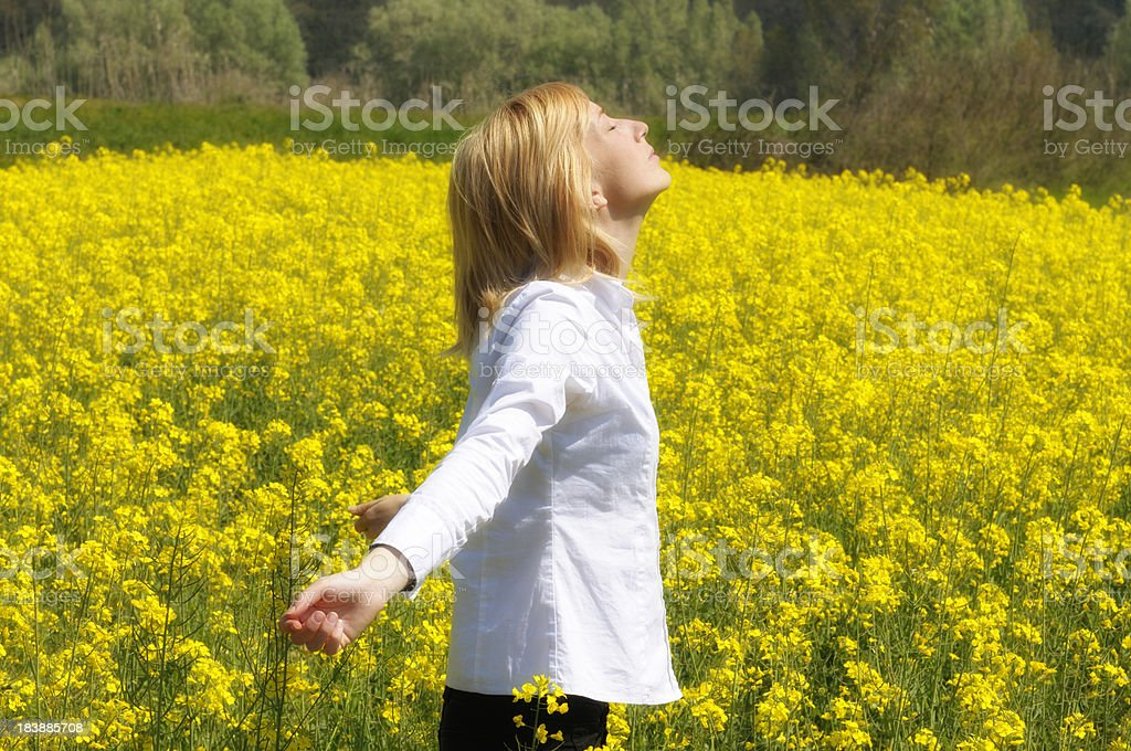 Girl Relaxing in Canola Field royalty-free stock photo