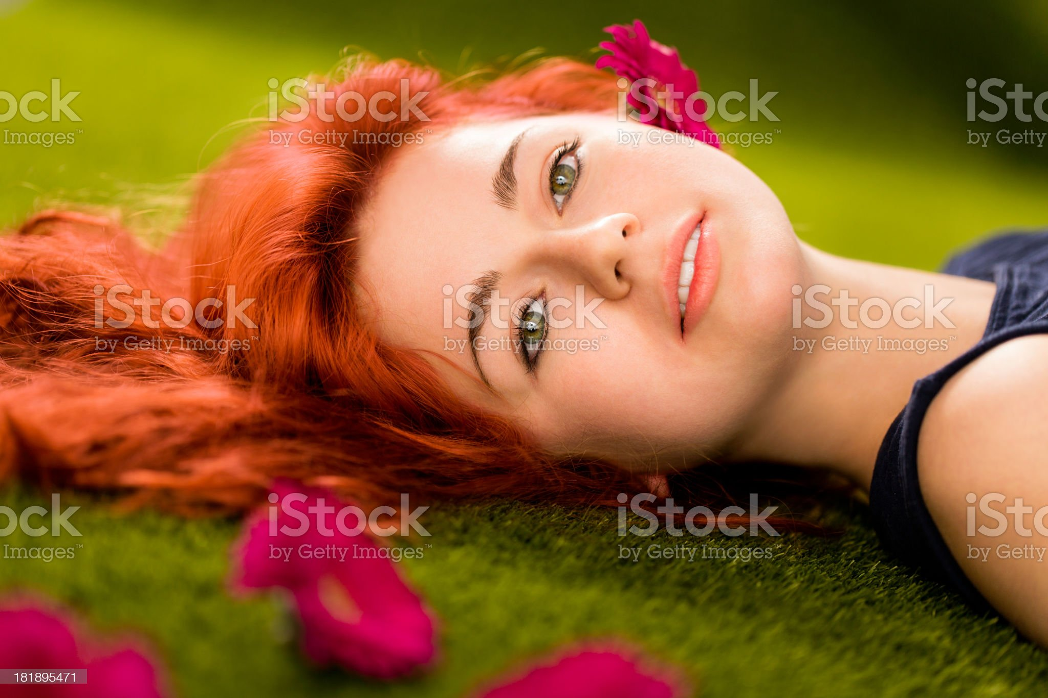 Girl relaxing in park with red blossoms royalty-free stock photo