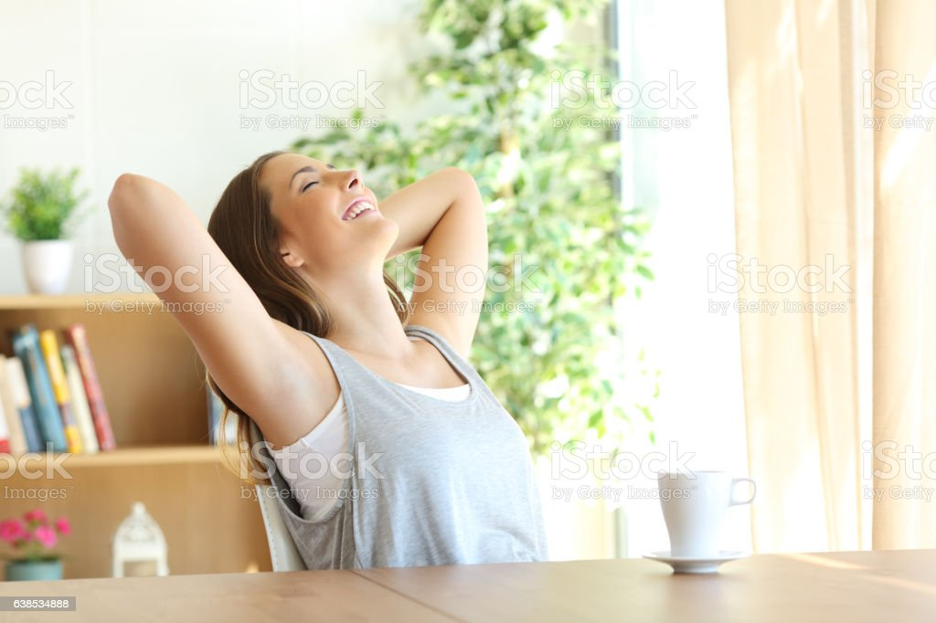 Girl relaxing on a chair at home stock photo