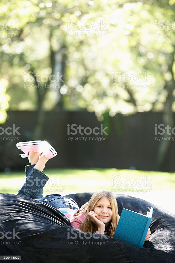 Girl relaxing with a book stock photo