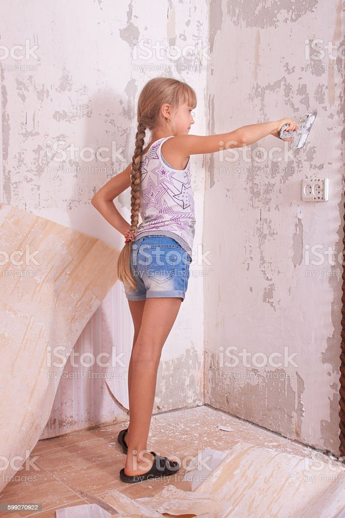 girl remove old wallpapers from wall stock photo