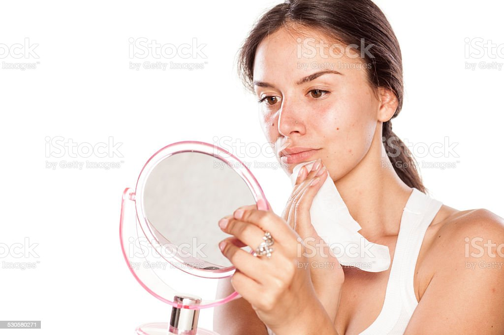 Girl removes her makeup with a wet tissue stock photo