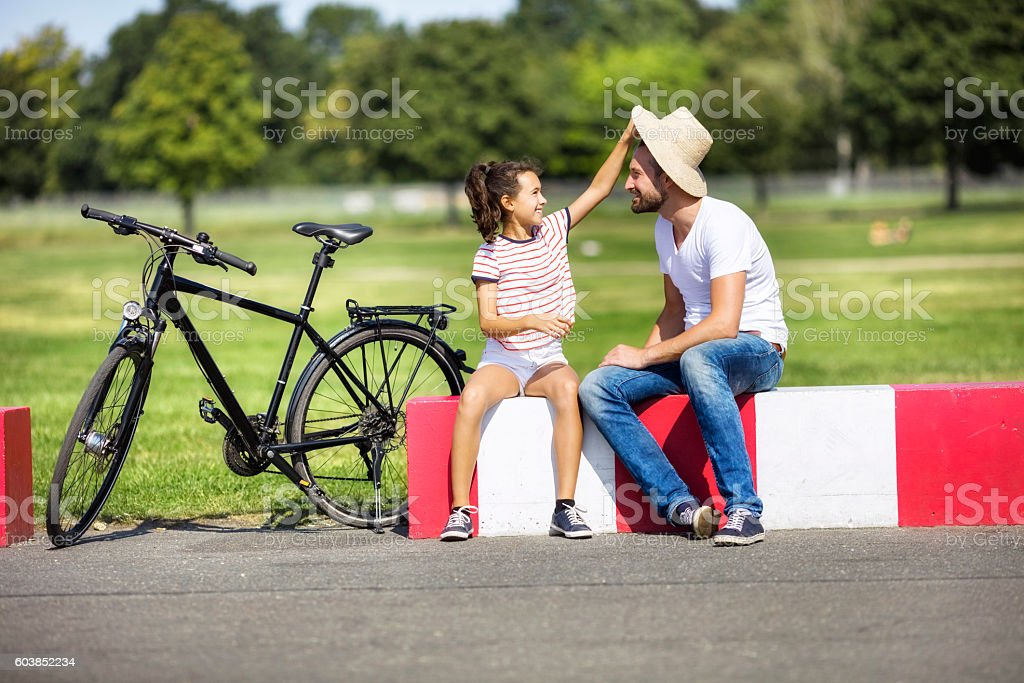 Girl removing father's hat while sitting by bicycle on roadside stock photo