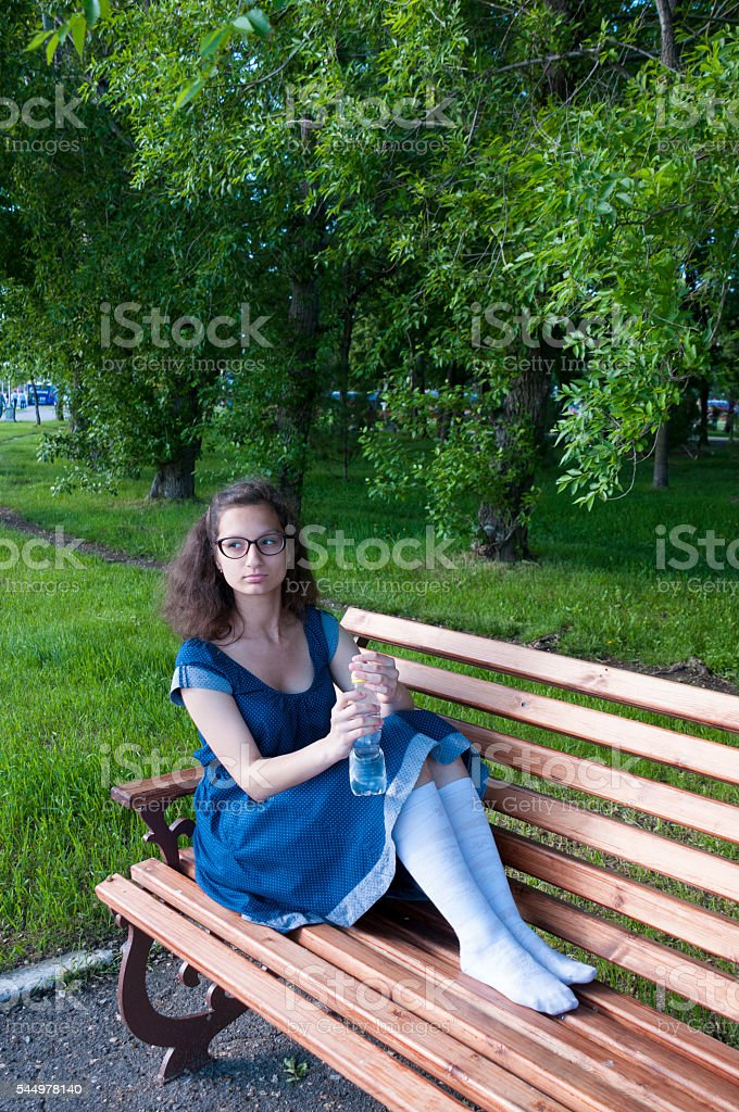 Girl resting in a park on a wooden bench stock photo