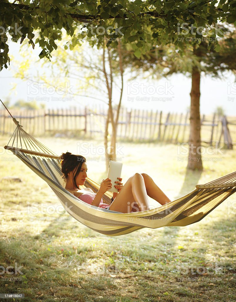girl resting in hammock, reading a tablet royalty-free stock photo