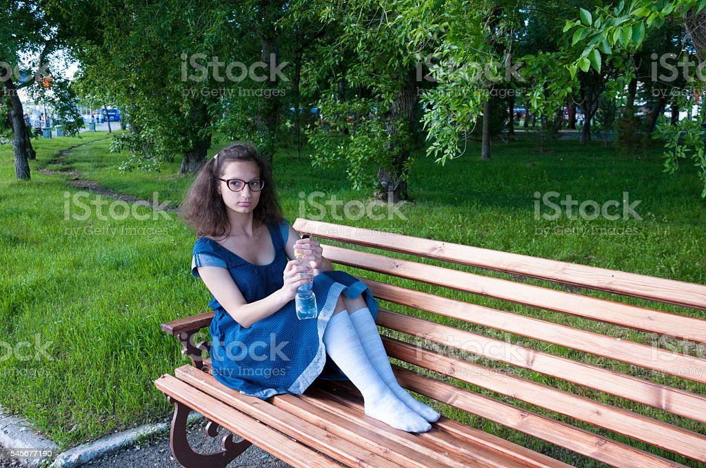 Girl resting on a bench and holding a water bottle stock photo