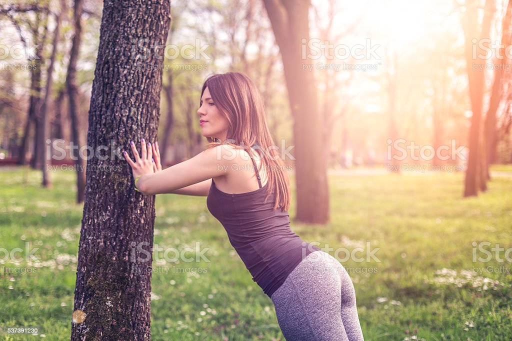 girl resting on a tree after running stock photo