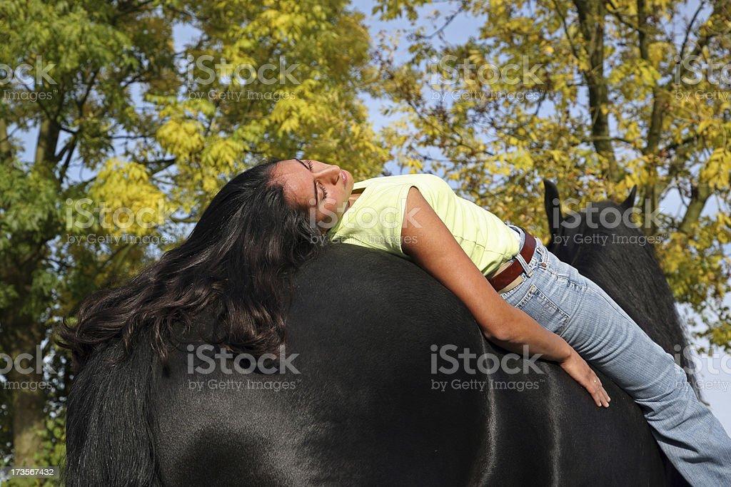 Girl resting on her horse stock photo