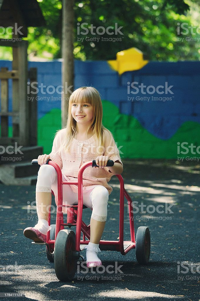 girl ridding a tricycle stock photo