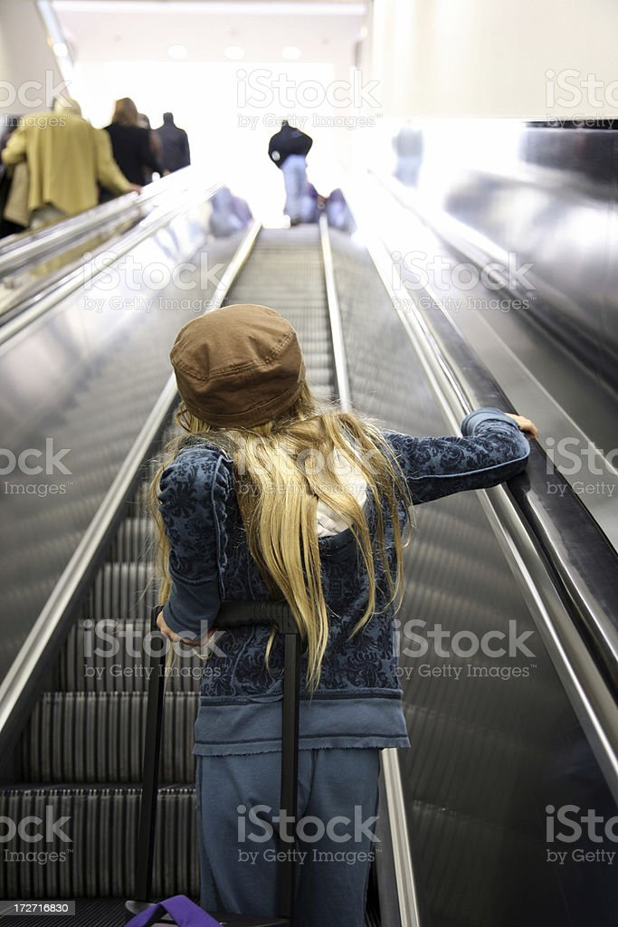 Girl rides on escalator in airport royalty-free stock photo