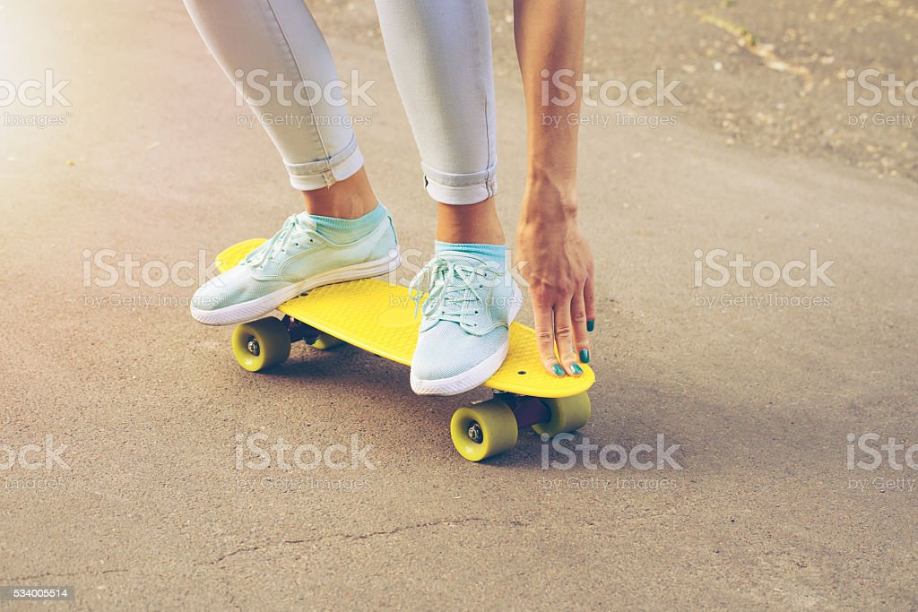 Girl rides on the road on a skateboard in sunlight royalty-free stock photo