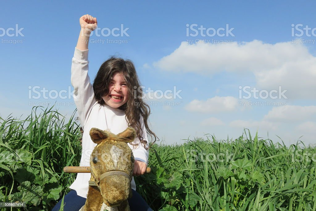 girl riding a toy horse stock photo