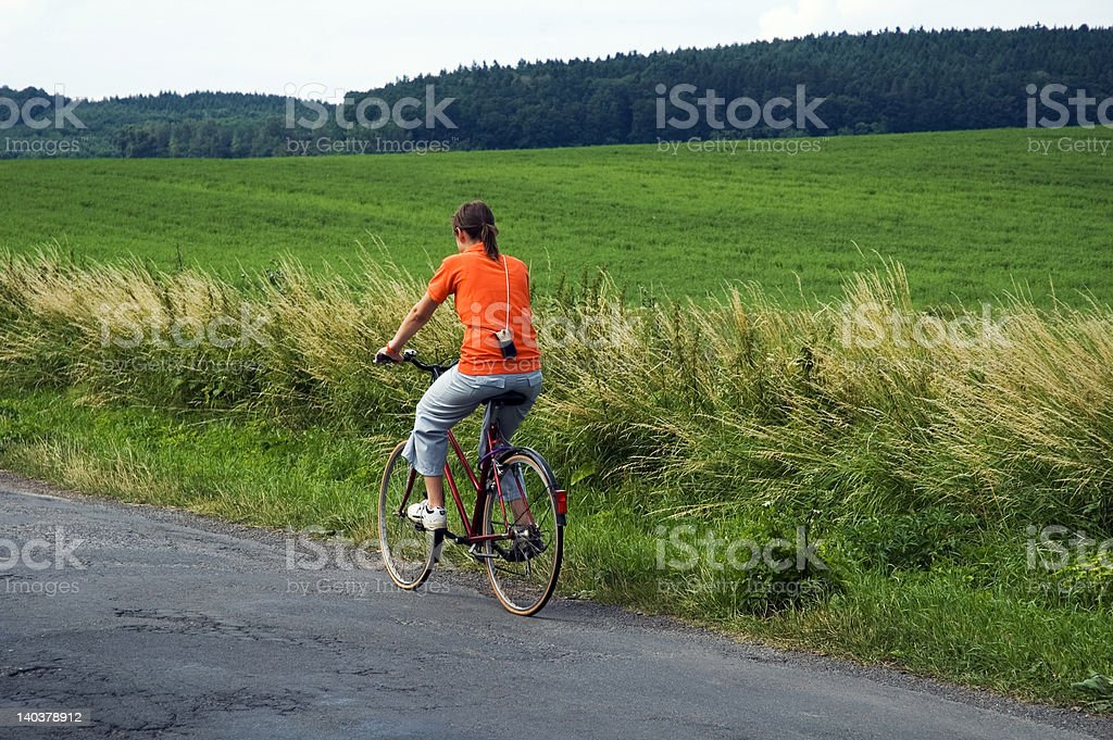 Girl riding bicycle on road through green field royalty-free stock photo