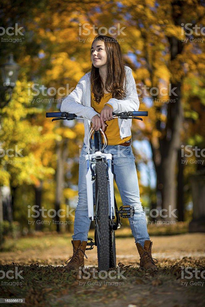 Girl riding bike in city park royalty-free stock photo