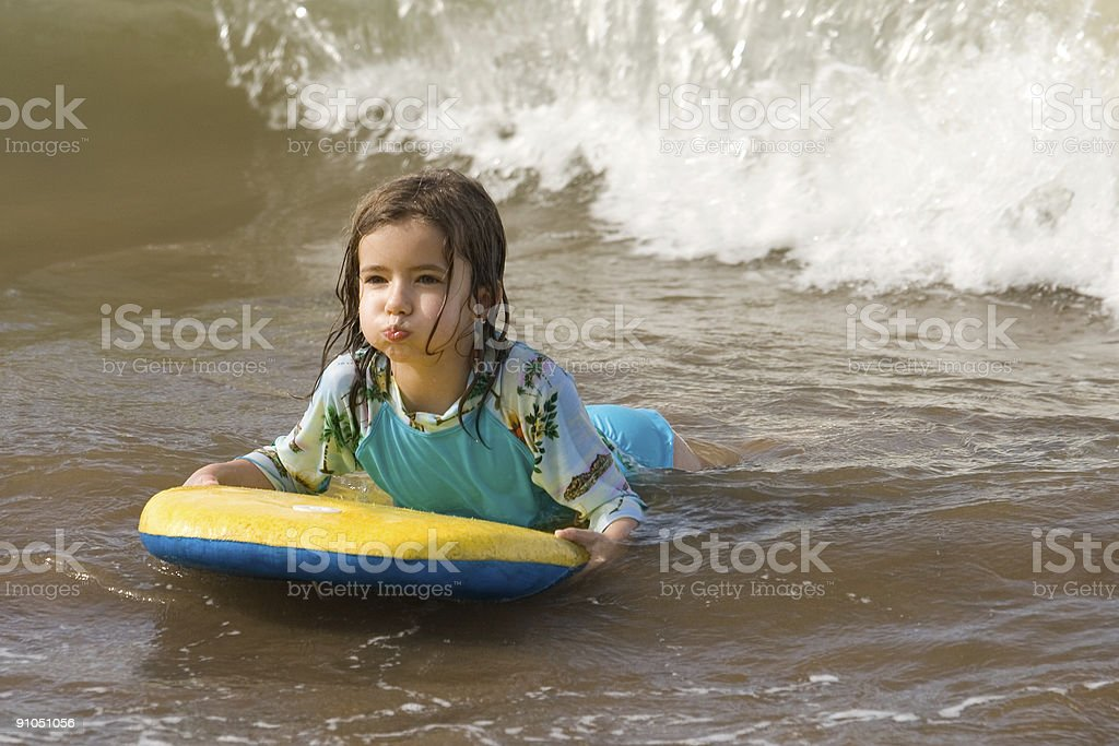 Girl riding boogie board in surf royalty-free stock photo