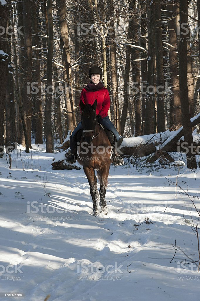 Girl riding horse in the snow stock photo