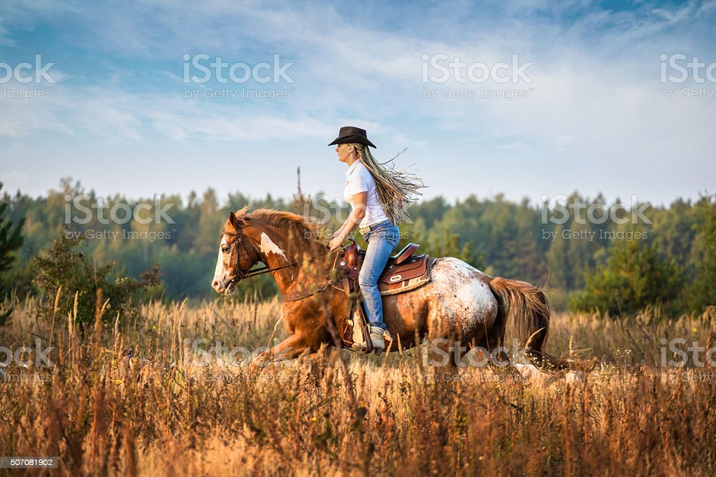 Girl riding on the Appaloosa horse stock photo