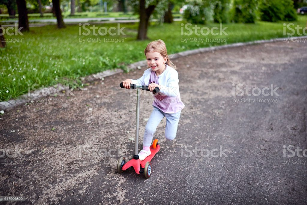 Girl riding push scooter stock photo