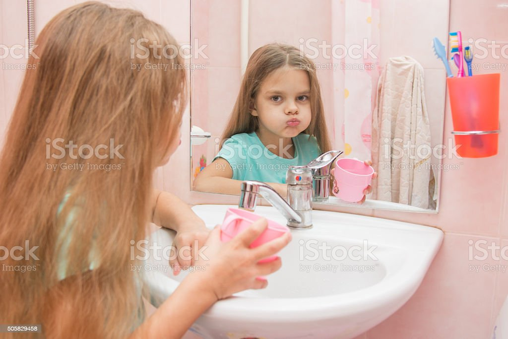 Girl rinse your mouth in the bathroom stock photo