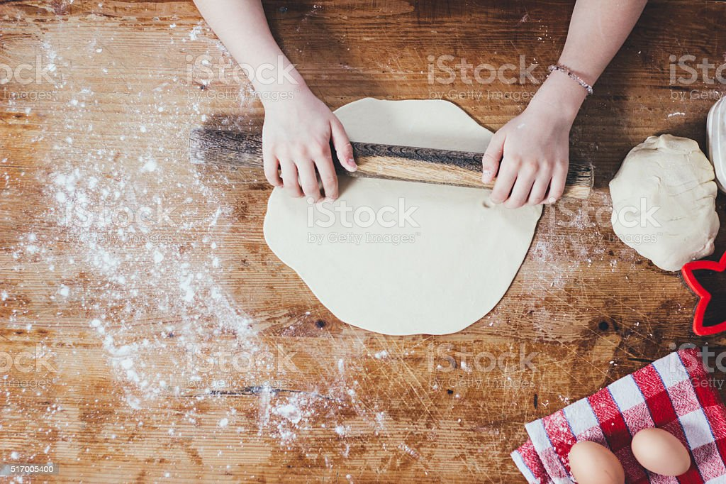 Girl rolling dough with rolling pin stock photo