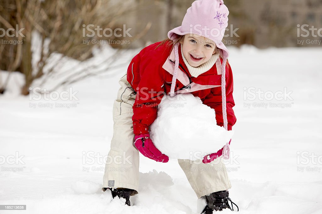 Girl rolling snowball for making Snowman stock photo