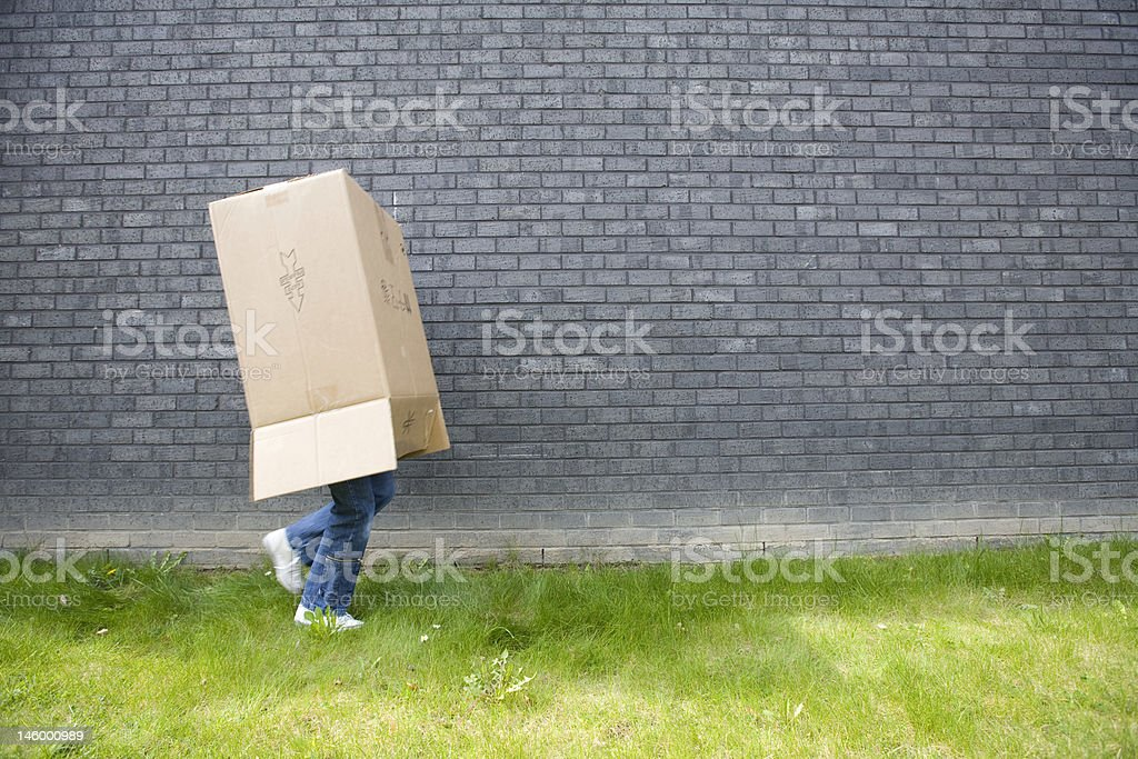 girl running away with a cardboard box over her head stock photo