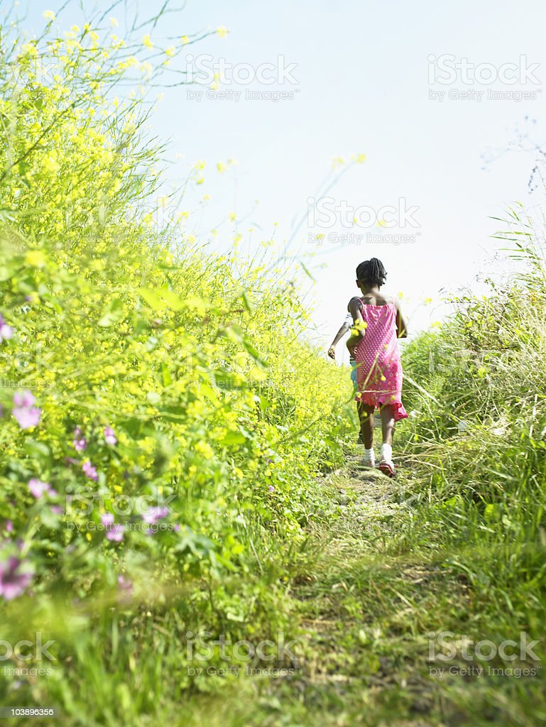 Girl running in long grass royalty-free stock photo