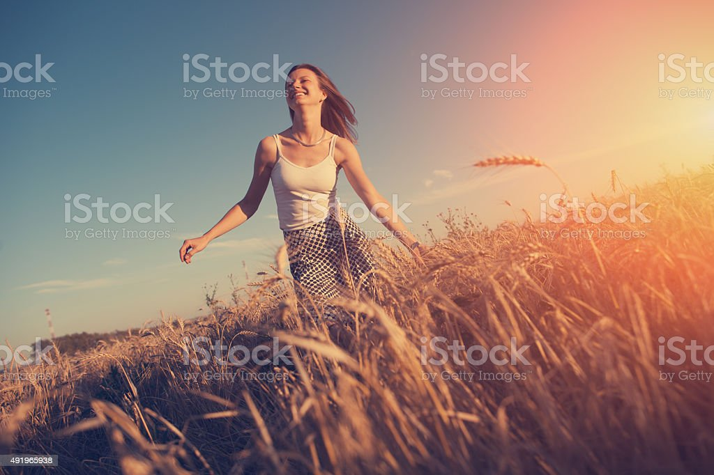 Girl running in the field at sunset stock photo