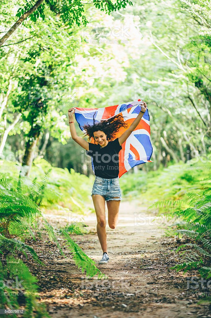 Girl running in the forest with an English Flag stock photo