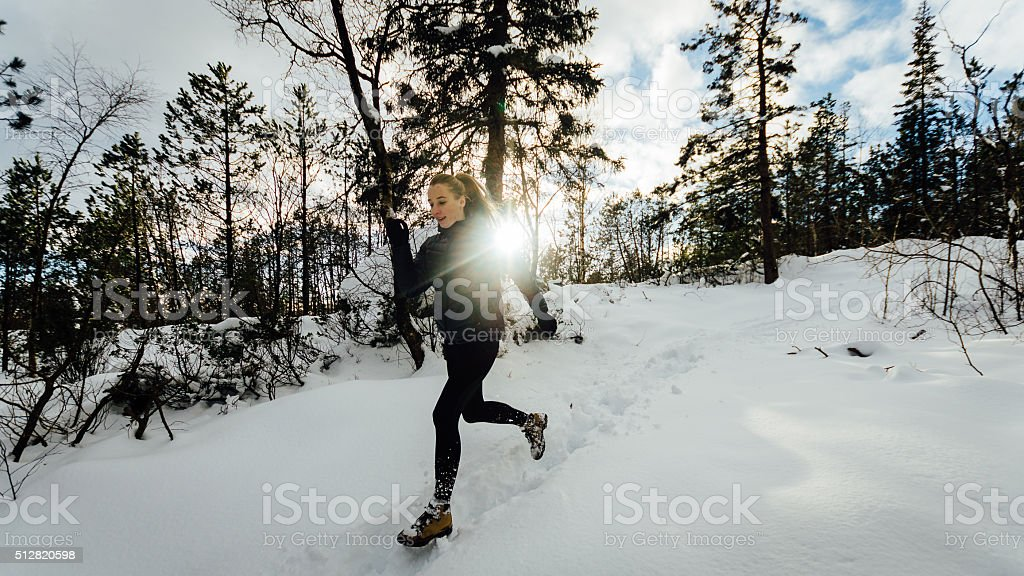 Girl running in winter forest stock photo