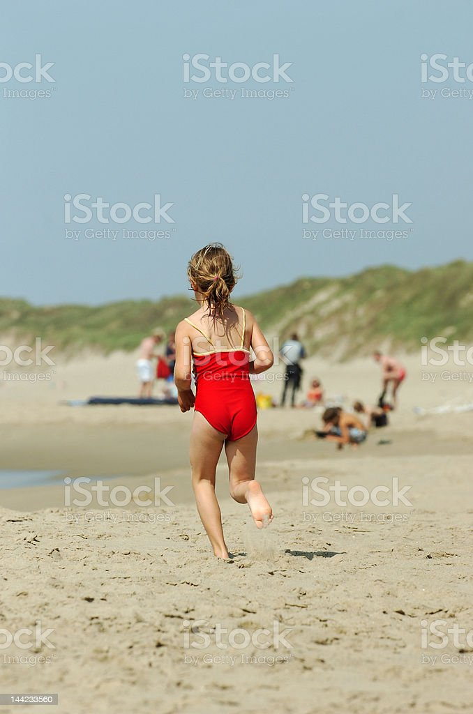 girl running on beach stock photo