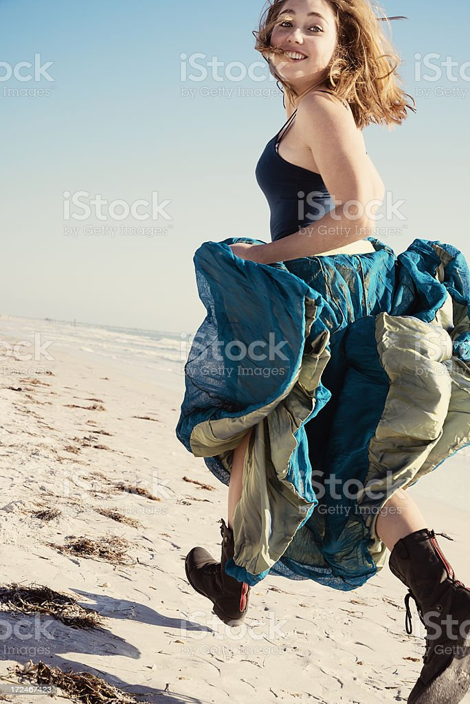 Girl running on beach with long skirt royalty-free stock photo